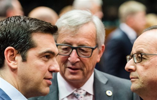 Greek Prime Minister Alexis Tsipras, left, speaks with European Commission President Jean-Claude Juncker, center, and French President Francois Hollande during a meeting of eurozone heads of state at the EU Council building in Brussels on Sunday, July 12,