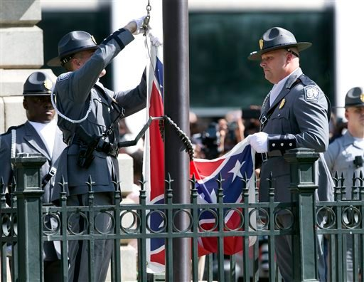 In this Friday, July 10, 2015, file photo, an honor guard from the South Carolina Highway patrol lowers the Confederate battle flag as it is removed from the Capitol grounds in Columbia, S.C. Legions of people clapped, cheered and cried as South Carolina