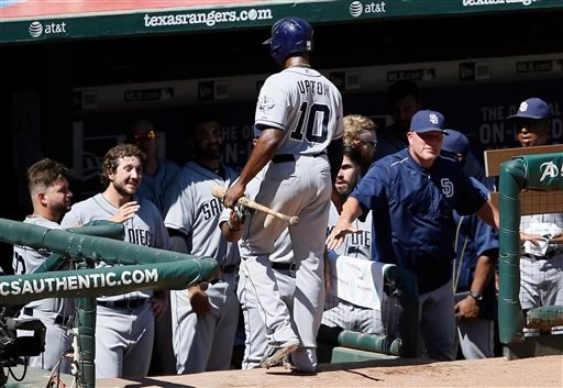 San Diego Padres' Justin Upton (10) is congratulated at the dugout after scoring on a Jedd Gyorko single to left against the Texas Rangers in the seventh inning of an interleague baseball game Sunday, July 12, 2015, in Arlington, Texas. (AP Photo/Tony Gut