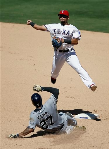 Texas Rangers second baseman Rougned Odor throws to first for the double play attempt after forcing San Diego Padres' Matt Kemp in the seventh inning of an interleague baseball game, Sunday, July 12, 2015, in Arlington, Texas. The Padres' Justin Upton was