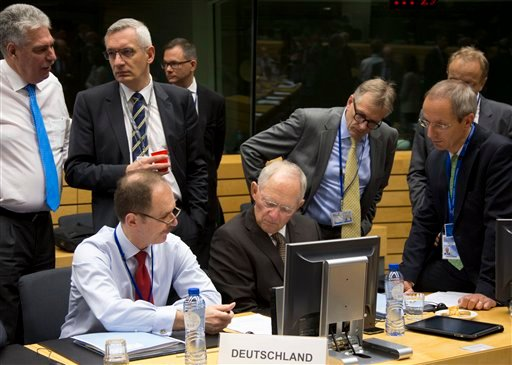 German Finance Minister Wolfgang Schaeuble, sitting center, goes over papers with members of his delegation during a round table meeting of eurogroup finance ministers at the EU Lex building in Brussels on Sunday, July 12, 2015. Greece has another chance
