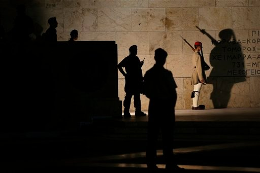 A presidential guard, right, stands guard at the tomb of the unknown soldier as riot police officers guard one of the entrances to the parliament during a demonstration of supporters of the no vote in central Athens, Sunday, July 12, 2015. Greece has anot