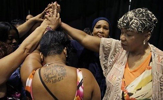 AP- In this July 8, 2015 file photo, Gwen Carr, mother of Eric Garner, right, joins women whose families members were killed by police officers .