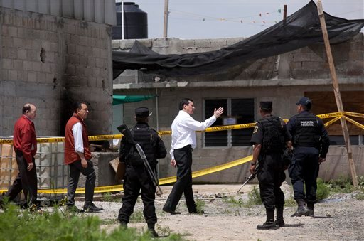 """Mexico's Interior Secretary Miguel Angel Osorio Chong, white shirt, arrives to the half-built house where drug lord Joaquin """"El Chapo"""" Guzman made his escape through a tunnel from the Altiplano maximum security prison in Almoloya, west of Mexico City, Mon"""