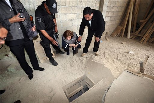 """In this photo provided by Mexico's attorney general, authorities inspect the exit of the tunnel they claim was used by drug lord Joaquin """"El Chapo"""" Guzman to break out of the Altiplano maximum security prison in Almoloya, west of Mexico City, Sunday, July"""