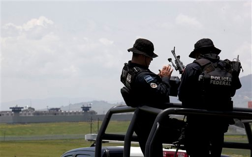 """Federal Police man their weapons aboard a pick up truck, near the half-built house where drug lord Joaquin """"El Chapo"""" Guzman made his escape through a tunnel from the Altiplano maximum security prison in Almoloya, west of Mexico City, Monday, July 13, 201"""