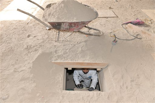 """A forensics worker climbs up a ladder leading to the exit of the tunnel that was used by Mexican drug lord Joaquin """"El Chapo"""" Guzman."""