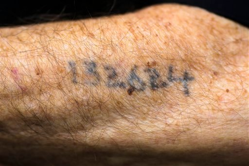 Auschwitz survivor Leon Schwarzbaum shows his tattooed number to the photographer as he waits to enter the court room for the judgment at the trail against former SS guard Oskar Groening in Lueneburg, Germany, Wednesday, July 15, 2015. Groening, 94, who s