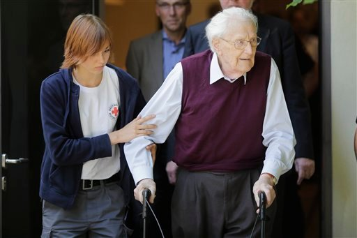 With the help of a Red Cross worker, former SS guard Oskar Groening, right, leaves the court after the verdict of his trial in Lueneburg, Germany, Wednesday, July 15, 2015. Groening, 94, who served at the Auschwitz death camp was convicted on 300,000 coun