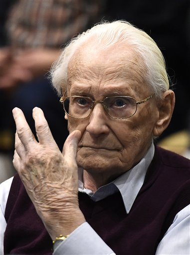 94-year-old former SS sergeant Oskar Groening gestures as he listens to the verdict of his trial Wednesday, July 15, 2015 at a court in Lueneburg, northern Germany. Groening, who served at the Auschwitz death camp was convicted on 300,000 counts of access