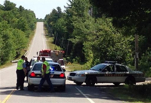 Law enforcement officers man at checkpoint Friday, July 17, 2015, in Lee, Maine.