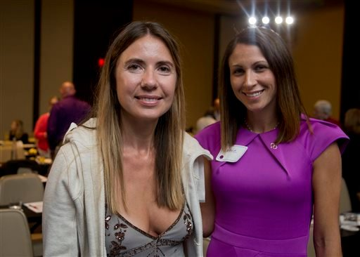Giedre Cohen, 37, of Calabasas, Calif., and Carrie Richardson, 34, of Montgomery, Ala., pose for a picture during a break at the Alzheimer's Association International Conference in Washington, Saturday, July 18, 2015. Saturday for the first time, research