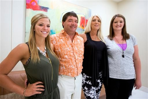 Dean DeMoe, second from left, with his family, from left, daughter McKenna DeMoe, 19, wife, Deb Demoe, and daughter Lindsey Sarkilahti, 29, pose for a picture at the Alzheimer's Association International Conference in Washington, Saturday, July 18, 2015.