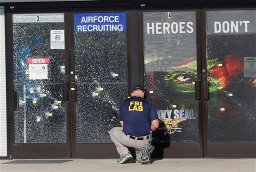 In this July 17, 2015 file photo, an FBI investigator investigates the scene of a shooting outside a military recruiting center in Chattanooga, Tenn. The deadly shootings of Marines at two Tennessee military sites illustrate the threat FBI officials in re