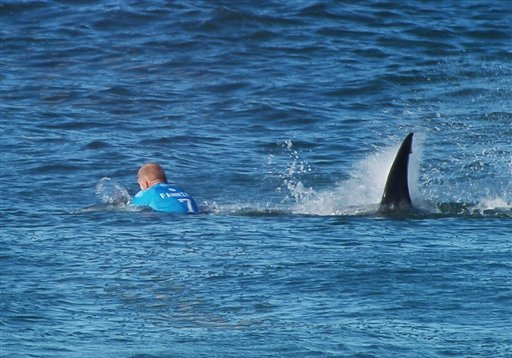 In this image made available by the World Surf League, Australian surfer Mick Flanning is pursued by a shark, in Jeffrey's Bay, South Africa, Sunday, July 19, 2015. Knocked off his board by an attacking shark, a surfer punched the creature during the tele