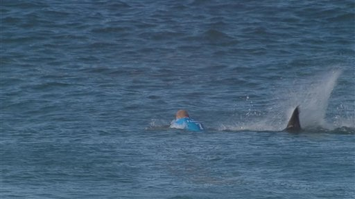 In this screen shot taken from video made available by the World Surf League, Australian surfer Mick Flanning is pursued by a shark, in Jeffrey's Bay, South Africa, Sunday, July 19, 2015. Knocked off his board by an attacking shark, a surfer punched the c