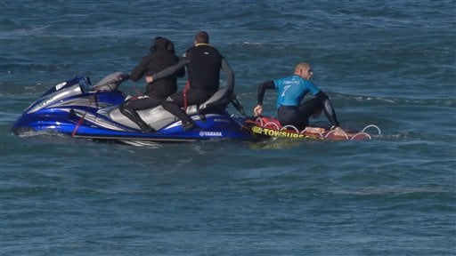 In this screen shot taken from video made available by the World Surf League, Australian surfer Mick Flanning sits on board a rescue boat after being pursued by a shark, in Jeffrey's Bay, South Africa, Sunday, July 19, 2015. Knocked off his board by an at
