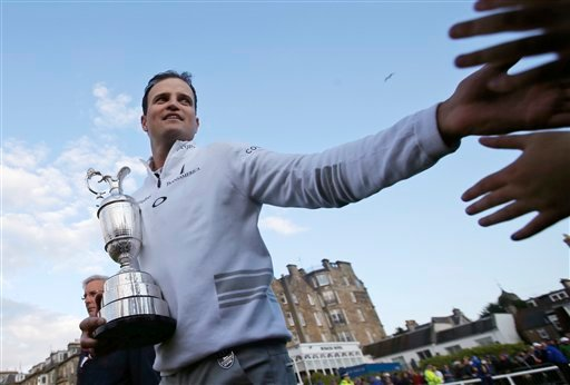 United States' Zach Johnson celebrates with members of the public as he holds the trophy after winning a playoff after the final round at the British Open Golf Championship at the Old Course, St. Andrews, Scotland, Monday, July 20, 2015.