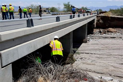 Inspectors for the California Department of Transportation inspect a west bound bridge for damage next to the bridge that was washed out along Interstate 10 in Southern California, Monday, July 20, 2015. All traffic along one of the major highways connect