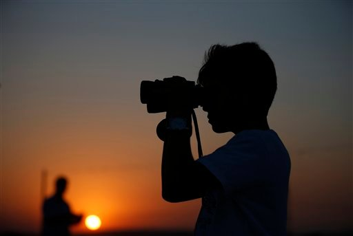 A youth uses binoculars to look at Turkish army tanks holding positions, near the border with Syria, in the outskirts of the village of Elbeyi, east of the town of Kilis, in southeastern Turkey, Thursday, July 23, 2015. Suspected Islamic State militants f