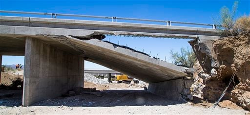 Construction workers stand near the collapsed elevated section of Interstate 10, Wednesday, July 22, 2015, near Desert Center, Calif. (Tom Tingle/The Arizona Republic via AP)