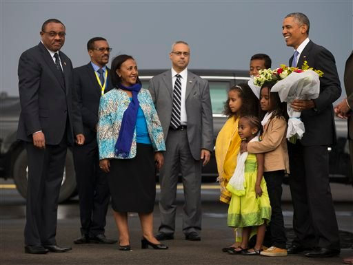 Ethiopian Prime Minister Hailemariam Desalegn, left, looks on as President Barack Obama is given a bouquet of flowers as he arrives at Addis Ababa Bole International Airport, on Sunday, July 26, 2015, in Addis Ababa. Obama is the first sitting U.S. presid