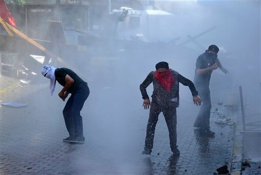 Left-wing protesters try to avoid tear gas and water used by police to disperse them, in Istanbul, Sunday, July 26, 2015, during clashes between police and people protesting against Turkey's operation against Kurdish militants. Turkey has bombed Islamic S