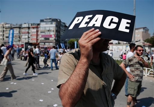 A protester holds a placard to protect himself from the sun during a rally in Istanbul, Sunday, July 26, 2015 to denounce the deaths of 32 people in a suicide bombing attack Monday in Suruc, southeastern Turkey, near the border with Syria. Turkey has subs