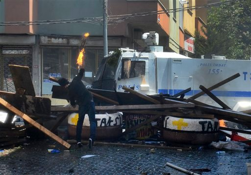 A left-wing protester hurls a petrol bomb towards a police car, behind a makeshift barricade background, In Istanbul, Sunday, July 26, 2015, during clashes between police and people protesting against Turkey's operation against Kurdish militants.Turkey ha