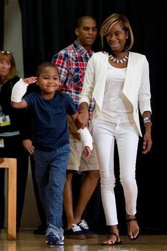 Double-hand transplant recipient eight-year-old Zion Harvey arrives to a news conference with his mother Pattie Ray Tuesday, July 28, 2015, at The Children's Hospital of Philadelphia (CHOP) in Philadelphia. Surgeons said Harvey of Baltimore who lost his l