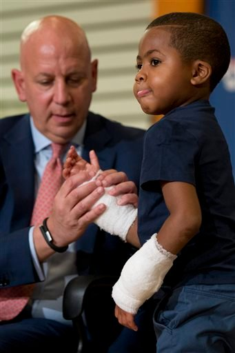 As Dr. L. Scott Levin holds his hand, double-hand transplant recipient eight-year-old Zion Harvey moves his fingers during a news conference Tuesday, July 28, 2015, at The Children's Hospital of Philadelphia (CHOP) in Philadelphia. Surgeons said Harvey of