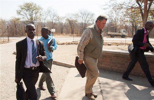 Theodro Bronkhorst, centre, a professional hunter, arrives for his appearance at the magistrates courts in Hwange about 700 kilometres south west of Harare, Wednesday, July 29, 2015.