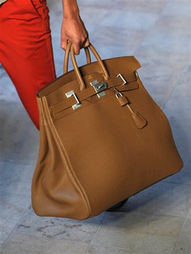 This Saturday, June 25, 2011 file photo shows a model carrying a Birkin handbag as he wears a creation by French fashion designer Veronique Nichanian for Hermes collection as part of spring-summer 2012 men's fashion, presented in Paris, France.