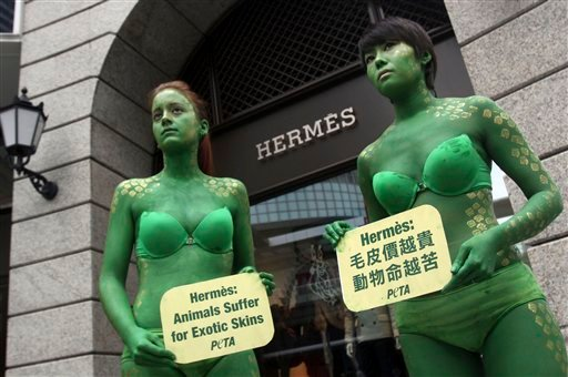 This Thursday, Oct. 20, 2011file photo shows activists from People for the Ethical Treatment of Animals (PETA) Asia, with their bodies painted, holding signs against French fashion house Hermes' use of animal skins in Taipei, Taiwan.