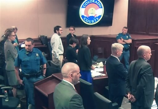 In this image made from Colorado Judicial Department video, James Holmes, background fifth from left in white shirt. Wednesday, July 29, 2015. (Colorado Judicial Department via AP, Pool)