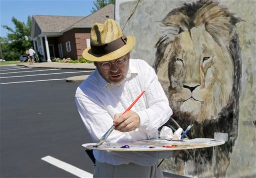 Mark Balma works on a mural of Cecil the lion outside Dr. Walter James Palmer's dental office in Bloomington, Minn., Wednesday, July 29, 2015.