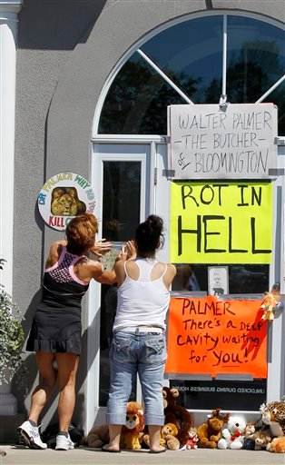 Women add signs to the door outside Dr. Walter James Palmer's dental office in Bloomington, Minn., Wednesday, July 29, 2015.