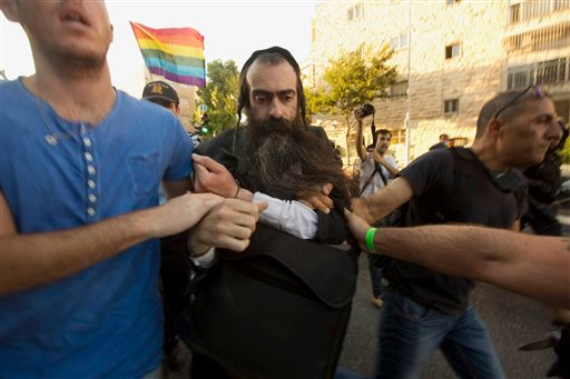 Ultra Orthodox Jew Yishai Schlissel is detained by plain-clothes police officers after he stabbed people during a gay pride parade in Jerusalem on Thursday, July 30, 2015.