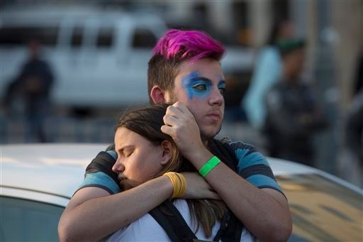 People react after an ultra-Orthodox Jew attacked people with a knife during a Gay Pride parade Thursday, July 30, 2015 in central Jerusalem. Israeli police said several people were stabbed.