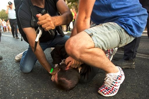A police officer removes a knife from ultra-Orthodox Jew Yishai Schlissel after he stabbed people during a gay pride parade in Jerusalem on Thursday, July 30, 2015.