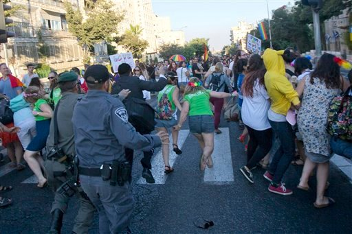 Israeli security forces reach for ultra-Orthodox Jew Yishai Schlissel attacking people with a knife during a Gay Pride parade Thursday, July 30, 2015 in central Jerusalem. Israeli police said several people were stabbed.