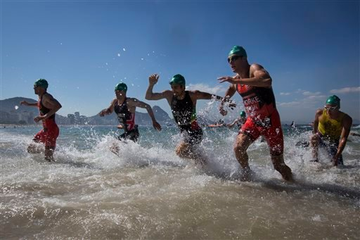 Triathletes exit the water during the men's triathlon ITU World Olympic Qualification Event in Rio de Janeiro, Brazil, Sunday, Aug. 2, 2015. The World Olympic Qualification is a test event for the Rio 2016 Olympics. (AP Photo/Felipe Dana)