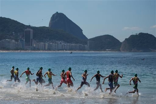 Triathletes enter the water at the start of the men's triathlon ITU World Olympic Qualification Event in Rio de Janeiro, Brazil, Sunday, Aug. 2, 2015. The World Olympic Qualification is a test event for the Rio 2016 Olympics. (AP Photo/Felipe Dana)