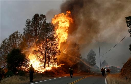 Firefighters spray a hose at a fire along Morgan Valley Road near Lower Lake, Calif., Friday, July 31, 2015. A series of wildfires were intensified by dry vegetation, triple-digit temperatures and gusting winds. (AP Photo/Jeff Chiu)
