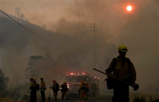 Firefighters walk under smoke from fires along Morgan Valley Road near Lower Lake, Calif., Friday, July 31, 2015. A series of wildfires were intensified by dry vegetation, triple-digit temperatures and gusting winds. (AP Photo/Jeff Chiu)