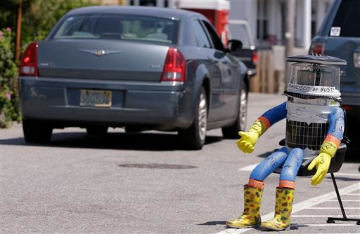 In this July 17, 2015, file photo, a car drives by HitchBOT, a hitchhiking robot in Marblehead, Mass. The Canadian researchers who created hitchBOT as a social experiment say someone in Philadelphia damaged the robot beyond repair on Saturday, Aug. 1, end