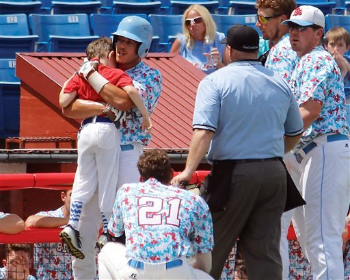 In this Aug. 1, 2015, photo, Liberal's Gavin Wehby holds Bee Jays batboy Kaiser Carlile moments after the 9-year-old was accidentally hit in the head during a National Baseball Congress World Series game in Wichita, Kan.