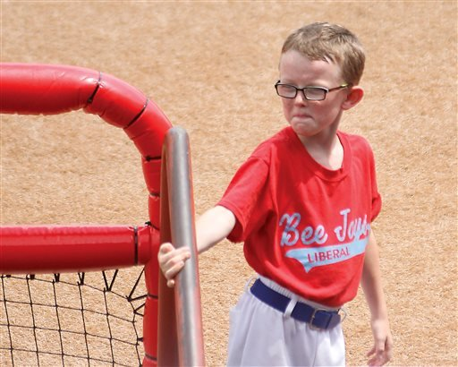 In this Aug. 1, 2015, photo, bat boy Kaiser Carlile, 9, gets ready for a National Baseball Congress World Series baseball game between the Liberal Bee Jays and San Diego Waves outside the dugout in Wichita, Kan.