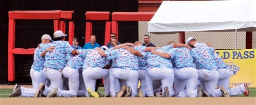 In this Aug. 1, 2015, photo, the Liberal Bee Jays team kneels in prayer near the outfield gate opened for an ambulance to transport Kaiser Carlile to a hospital at a National Baseball Congress World Series game in Wichita, Kan.