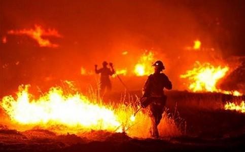 A firefighter lights a backfire as the Rocky Fire burns near Clearlake, Calif. AP